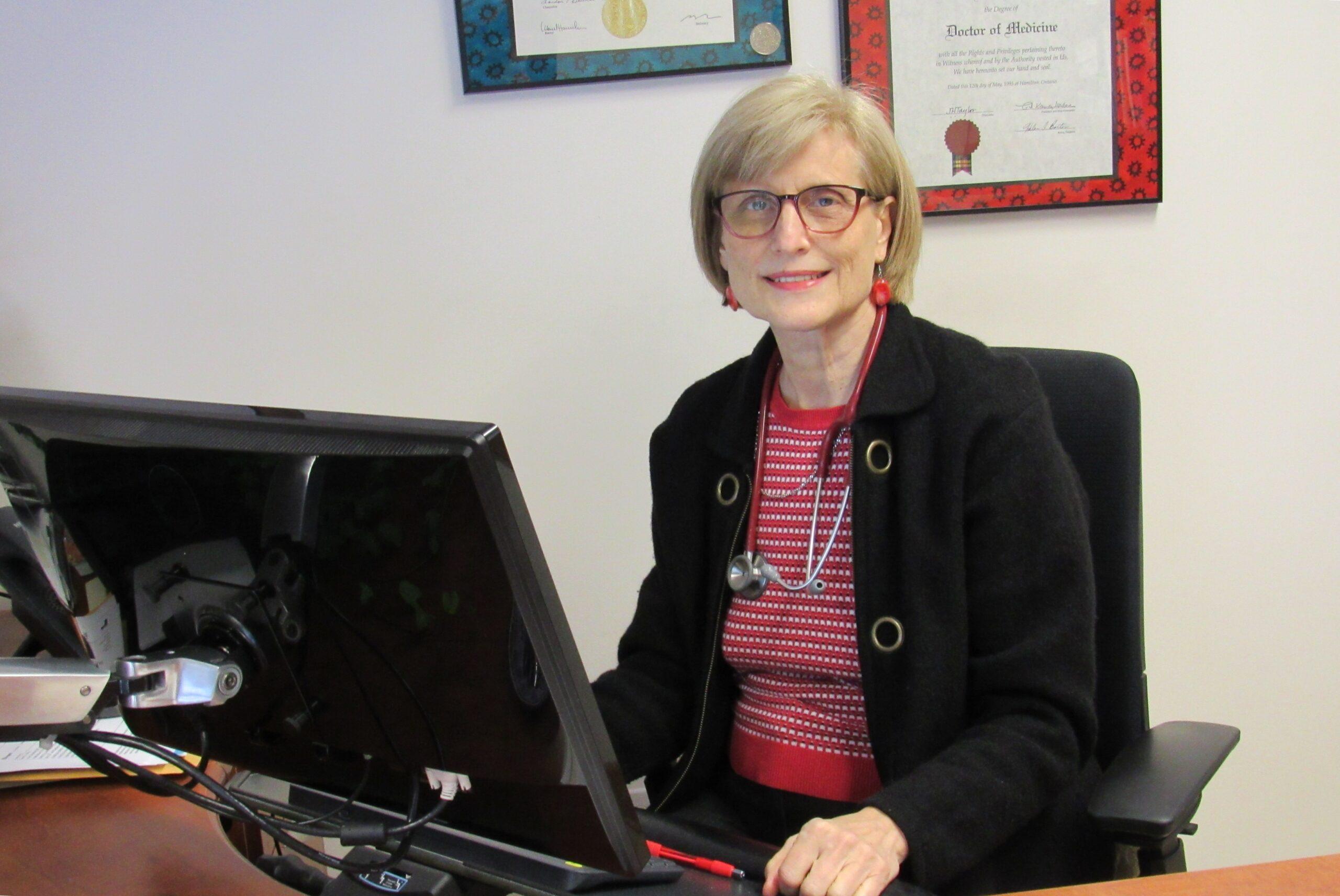 Dr. Elena Mihu at her desk smiling